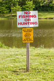 No fishing or hunting and No feeding signs on wooden post in nat Stock Photo