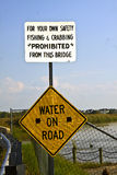 No Fishing Sign. Sign by bridge no fishing or crabbing and warning about water on road Stock Image