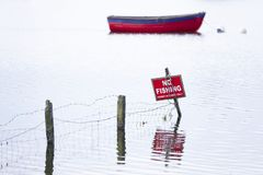 No fishing sign with boat in background on water lake. Uk stock photography