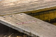No Fishing sign painted on a wooden deck in Provo. No Fishing sign painted on the weathered wooden deck in Provo, Utah. Dirty water can be seen beneath the stock photography