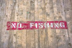 No Fishing sign painted on a wooden platform. Close up view of a red and white No Fishing sign painted on the surface of a wooden platform. Notice of royalty free stock photography