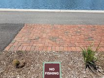 No fishing sign with red bricks and water. No fishing sign with red bricks and asphalt and water stock photos