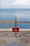 No Fishing sign. A `No Fishing` sign in the sand in front of the ocean, on a sunny afternoon, Florida, USA stock photo