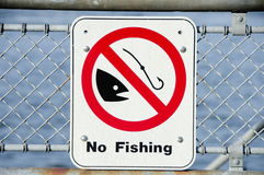 No Fishing Sign. On the side of the pier with chain link fence Royalty Free Stock Photography