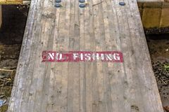No Fishing sign on wooden deck over murky water. Close up view of a wooden deck over murky water in Provo, Utah. A No Fishing sign is painted on the surface of royalty free stock image