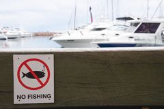 No fishing warning sign on wooden bench block for sitting in pie royalty free stock photo