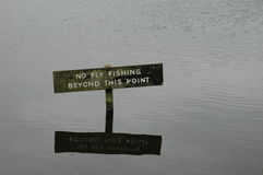No fly fishing sign in a lake. With the sign reflected Stock Photo