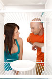 No food in fridge. Couple in front of fridge with no food having a domestic disagreement about shared marital responsibilities Royalty Free Stock Image