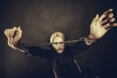 Furious man with chained hands, no freedom. No freedom, social problems concept. Furious man with chained hands, studio shot on dark grunge background Royalty Free Stock Image