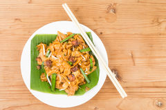 No frills simple Chinese Char Kway Teow or Fried Noodle on banana leaf. With cockerels royalty free stock photos