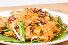 No frills simple Chinese Char Kway Teow or Fried Noodle on banana leaf. With cockerels Royalty Free Stock Photo