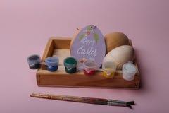 No fundo coral em uma caixa de madeira são as placas de madeira dos ovos cartão oval-dado forma roxo com uma Páscoa feliz da insc imagens de stock royalty free