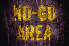 """No-Go Area"" danger warning sign in yellow letters painted over dark grungy concrete wall texture background stock photo"