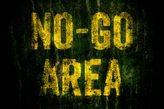 """No-Go Area"" warning sign in yellow letters painted over dark grungy concrete wall with moss stock photography"