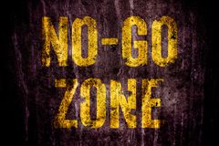 """No-Go Zone"" warning sign in yellow letters painted over dark grungy concrete wall texture background. royalty free stock photo"
