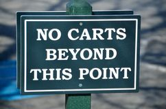 No golf carts sign. No carts beyond this point green and white golf course sign Royalty Free Stock Images