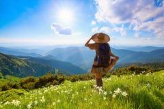 No gramado nas montanhas ajardina a menina do moderno no vestido Fotos de Stock