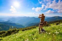 No gramado nas montanhas ajardina a menina do moderno no vestido Imagem de Stock