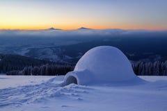 No gramado nevado no monte de neve há um iglu foto de stock