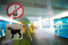 No guitar and free dog allowed sign. Stickers on transparent doors at the entrance of a international airport royalty free stock photography