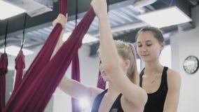 No gym a mulher estica seus pés na rede acima do assoalho vídeos de arquivo
