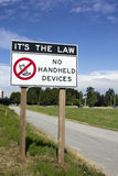 No Handheld Devices. A street sign warns motorist that useing handheld devices while driving is illegal Royalty Free Stock Images