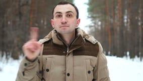 No, hombre joven que rechaza oferta agitando el finger contra el contexto del bosque del invierno almacen de video