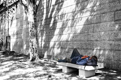 Homeless. A man sleeping on a stone bench by the Seine riverbank, Paris, France Royalty Free Stock Photo