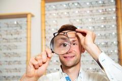 No homem novo da loja do ótico com a lente de aumento que seleciona a leitura nova fotos de stock