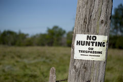 No hunting sign on post. No hunting sign on old post against green and blue background Stock Photos