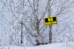 No hunting sign. Yellow and black no hunting sign posted in front of white frost covered trees Stock Photos