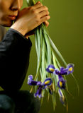 No, i do not wait. Young the man with a bouquet of irises in hands Royalty Free Stock Images