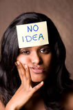 No idea brown. Portrait of a woman with a 'no idea' note on her forehead Royalty Free Stock Images