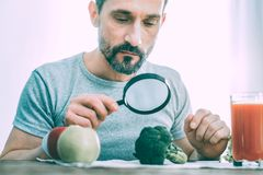 Indifferent calm man studying different types of vegetables stock photos