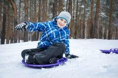No inverno nas madeiras, os trenós do menino na casa do gelo fotografia de stock royalty free