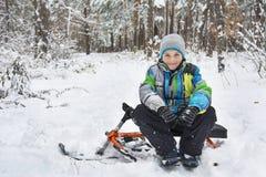 No inverno, o menino coberto de neve da floresta que senta-se em um pequeno trenó Imagem de Stock Royalty Free