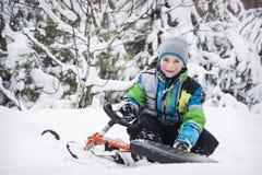 No inverno, o menino coberto de neve da floresta que senta-se em um pequeno trenó Imagens de Stock