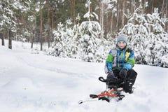 No inverno, o menino coberto de neve da floresta que senta-se em um pequeno trenó Imagem de Stock