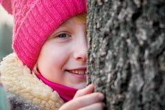 No inverno, uma moça olha e sorri atrás do tree_ Imagens de Stock