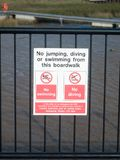 no jumping, diving or swimming from this boardwalk sign on railings at dock stock image