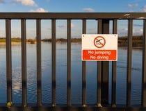 No Jumping No Diving Danger Hazard Warning Sign. Hazard warning sign on a bridge over a river saying No jumping. No diving stock photography