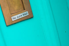 No junk mail sign. Gold letter box with silver label marked no junk mail in black lettering shown on green door stock photos