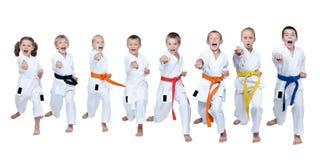 No karategi oito atletas estão batendo o gyaku-tsuki do perfurador foto de stock