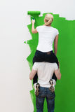 No ladder - no problem. As a clever young couple resort to a piggy back ride, view from behind Royalty Free Stock Images
