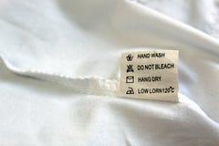 No lado seamy da roupa há uma etiqueta com instruções para o uso imagem de stock royalty free