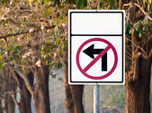 No left turn. Traffic sign no left turn again pink trumpet tree with flower in forest Stock Photo