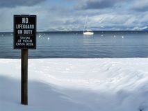 No Lifeguard on Duty. Snowy beach with No Lifeguard on Duty sign Stock Photo