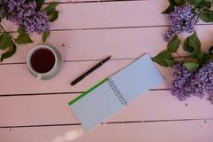 No lilás branco da tabela, presente, caderno, copo do chá Imagens de Stock Royalty Free