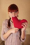 No Love. Girl furiously biting red heart stock image