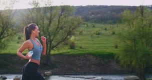No lugar de surpresa na jovem senhora da natureza que faz seu exercício que corre através da estrada da montanha feliz a que apre vídeos de arquivo